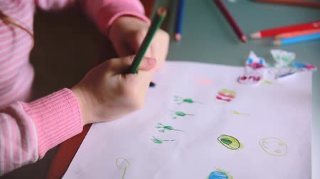 notas : Camera sliding left over little Caucasian preschool girl hands drawing animals with colorful pencils at a table close-up Stock Footage