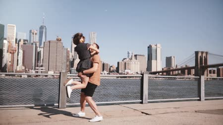 eufória : Happy Caucasian man meeting his girlfriend, hugging and smiling at sunny Manhattan skyline in New York City slow motion. Stock mozgókép