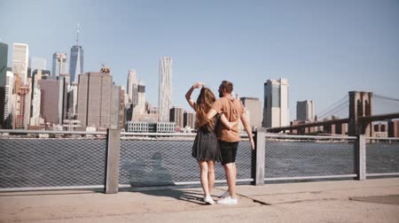 raised : Happy European tourist couple stand hugging, arms raised enjoying epic Manhattan view in New York, USA slow motion. Stock Footage