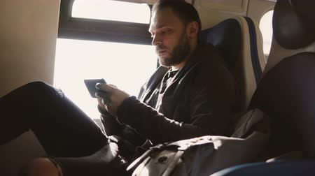 hírnök : Serious focused European freelance worker typing messages on smartphone messenger app traveling on the train window seat