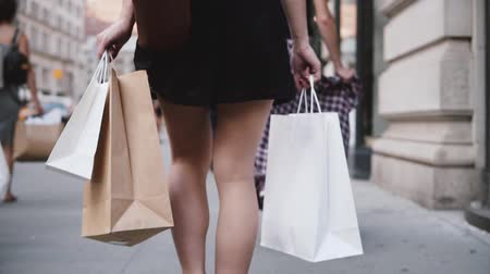 pitka : Back view of successful young girl addicted to shopping carrying bags in both hands walking along the street slow motion