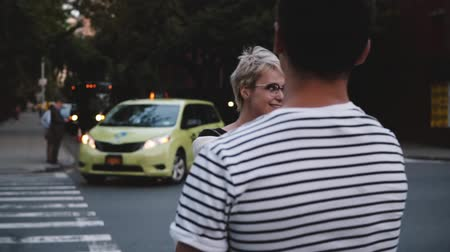 utca : Slow motion happy Caucasian girl leading boyfriend by the hand across the street smiling on romantic date in New York.