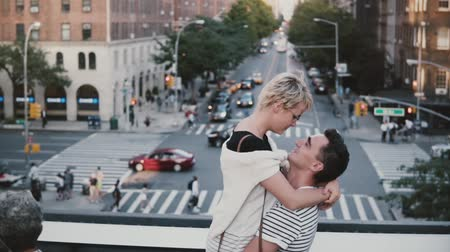 encerramento : Slow motion happy Hispanic man holding European girl in arms. Young romantic couple spinning on a bridge in New York.