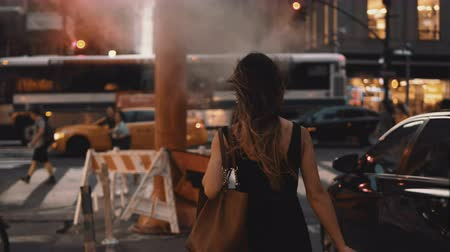 midtown manhattan : Young beautiful woman with shopping bags walking in downtown of New York, America, crossing the traffic road. Stock Footage