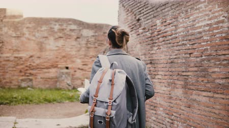 antikvitás : Camera follows young excited traveler woman with backpack expolring ancient historic red brick ruins of Ostia, Italy.
