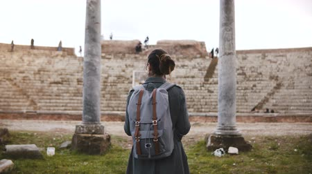 régészet : Back view of beautiful young female tourist with backpack and map exploring ancient amphitheater ruins in Ostia, Italy.