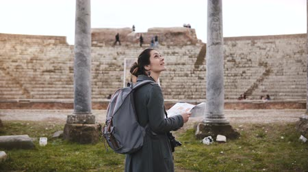 antikvitás : Back view of beautiful tourist girl with backpack standing in front of ancient amphitheater pillars in Ostia, Italy.