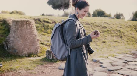 vacations cones : Young beautiful European female tour guide picking up a Pinea cone, giving it to senior women on a walking excursion. Stock Footage