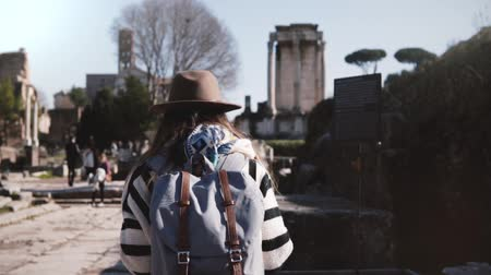 antikvitás : Young casual relaxed female tourist with backpack in stylish clothes walking at the Rome Forum enjoying the scenery.