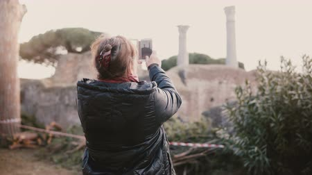 antikvitás : Back view of happy senior smiling Caucasian woman taking a smartphone photo of ancient ruins in Ostia, Italy on vacation Stock mozgókép