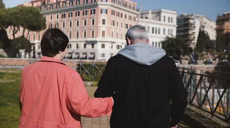 health insurance : Back view lovely romantic senior happy couple walking together holding hands on vacation in early autumn Rome, Italy. Stock Footage