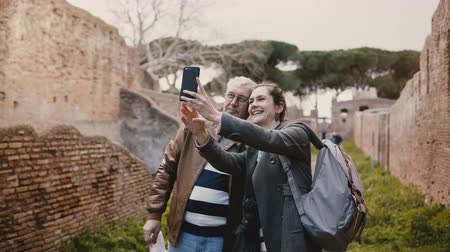wanderlust : Excited happy senior man and smiling European young woman taking selfie near old ruins in Ostia, Italy on vacation trip.
