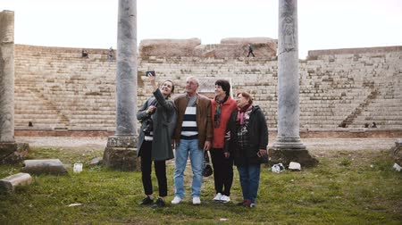 antikvitás : Smiling young European girl and happy senior tourist group taking selfie near old amphitheater ruins in Ostia, Italy. Stock mozgókép