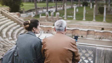 health insurance : Back view of young European girl and senior man sitting and talking at old ruins of antique Ostia amphitheater in Italy. Stock Footage