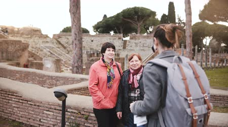 bedrijfsuitje : Young beautiful European girl taking a photo of two senior women near old historic ruins in Ostia, Italy on vacation.