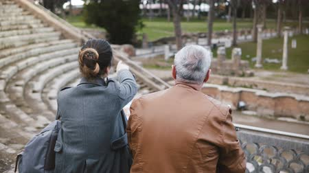 amfiteátr : Back view of European father and daughter sitting and talking at old ruins of antique Ostia amphitheater in Italy. Dostupné videozáznamy