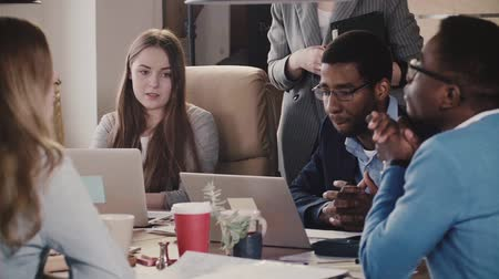 medezeggenschap : Confident young European female boss talks to multiethnic employees. Businesswoman leading office meeting by the table. Stockvideo