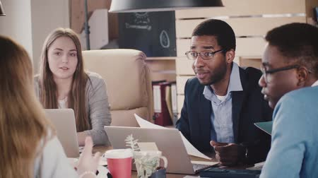 tartışıyor : Positive African American male CEO laughs at multiethnic office team meeting by the table in loft coworking slow motion. Stok Video