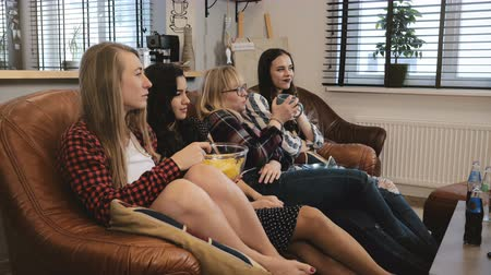 serial : Girlfriends watch romantic film on TV at home. Young attractive Caucasian girls watching melodrama emotional film 4K.