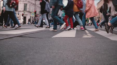 peoples : Low angle slow motion shot of peoples legs and feet crossing a busy city street, red bicycle passing close by camera. Stock Footage