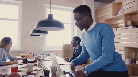 directional : Multiethnic colleagues talk in modern office. Young happy friendly business people talk, show gestures during break 4K. Stock Footage
