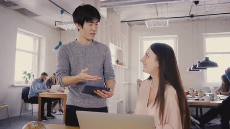 directional : Multiethnic colleagues talk in modern office. Young happy Asian man discussing work with beautiful Caucasian girl 4K.