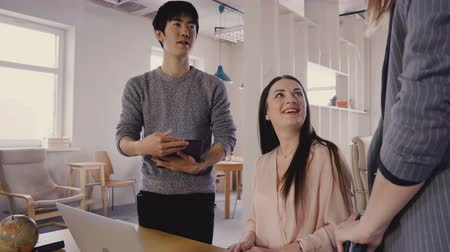 femminismo : Mixed race colleagues talk to female boss. Happy millennial workers smile and meet CEO in light trendy office space 4K. Filmati Stock