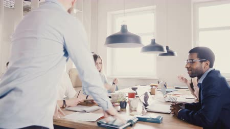 directional : Young European boss motivates and encourages colleagues. Happy multiethnic workers smile, enjoy modern healthy office 4K Stock Footage