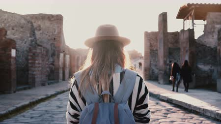 mítosz : Back view of girl in hat with backpack standing in the middle of ancient antique street in Pompeii, Italy on a sunny day