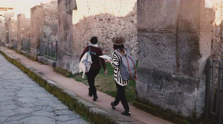 Camera follows two women with a map walking along old antique ruins and streets of Pompeii, Italy on travel vacation. Stock Footage
