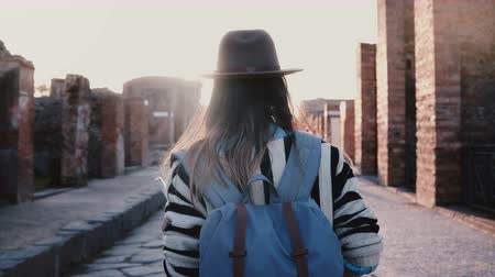 mítosz : Camera follows successful female travel blogger in hat with backpack walking along ancient street in Pompeii on sunset.