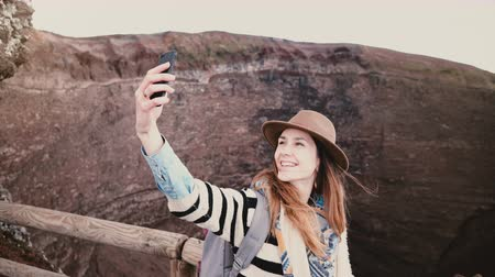 Young beautiful student girl with backpack smiling taking smartphone selfie photo on the edge of Vesuvius volcano crater Stock Footage