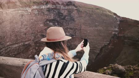vesuvio : Young happy freelancer girl with backpack taking smartphone photos of Vesuvius volcano crater on vacation in Italy.