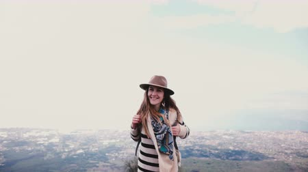 vesuvio : Excited beautiful tourist woman holding hat, turning to camera and smiling at epic mountain top scenery view on Vesuvius Filmati Stock