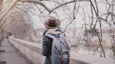 Beautiful slow motion shot of local girl with backpack walking along Tiber river under sycamore trees on a winter day.