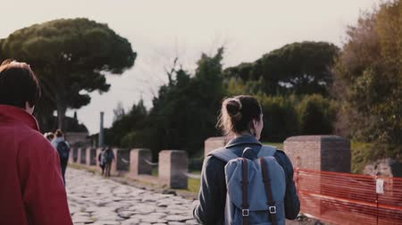 Young Caucasian female excursion tour guide showing antique ruins of Ostia, Italy to a senior woman tourist slow motion. Stock Footage