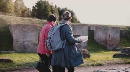 Side view of European mother and daughter with a map walking together along historic old town of Ostia slow motion. Stock Footage