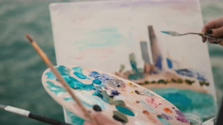 Closeup view of female hand with brush and palette painting the picture on the shore of Michigan lake, Chicago, America. Stock Footage