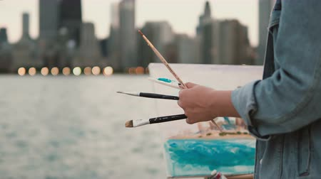 Young woman drawing the picture on the shore of Michigan lake, Chicago, America. Street artist using brushes and paint. Stock Footage