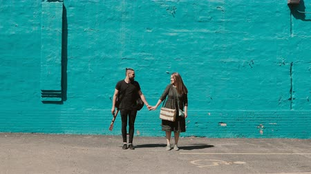 Young beautiful couple posing near the bright blue wall. Handsome man with guitar holds hand of woman with sketchbox.