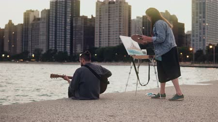Young creative couple of street artists doing hobby on shore of Michigan, Chicago, USA. Woman draws, man plays guitar. Stock Footage