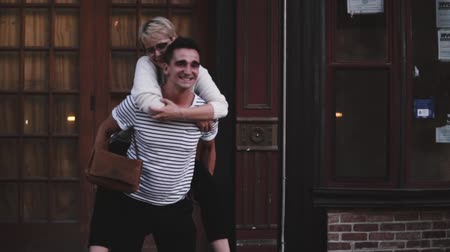 Slow motion happy young Hispanic man carrying his girlfriend on his back laughing, enjoying romantic fun date outside. Dostupné videozáznamy