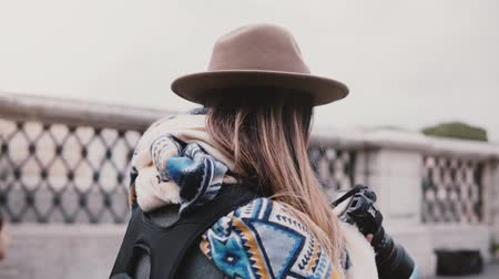 Back view close-up of professional female photographer with backpack in stylish clothes take photo of Rome slow motion.