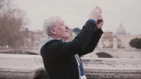 Happy smiling senior European man taking smartphone photo of Rome, Italy on retirement vacation trip slow motion.