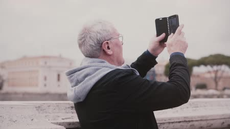 Happy excited senior male tourist taking a photo of ancient city buildings in Rome, Italy using smartphone slow motion. Dostupné videozáznamy