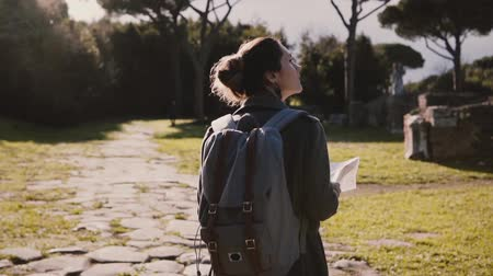 Back view of attractive travel blogger girl with backpack and map exploring ancient sunny ruins in Ostia slow motion.