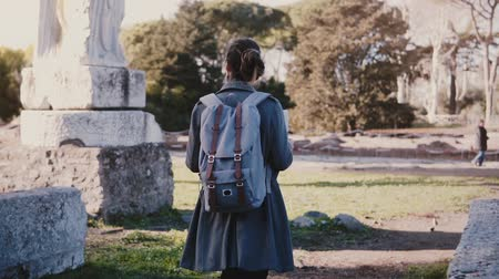 Camera follows young female tourist with backpack enjoying amazing antique ruins of Ostia Antica, Italy slow motion.