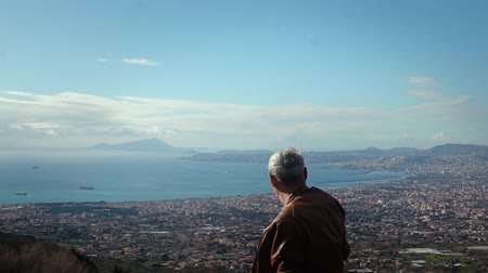 Happy active senior Caucasian male tourist enjoying epic view panorama of sunny Naples from Vesuvius, Italy slow motion. Dostupné videozáznamy