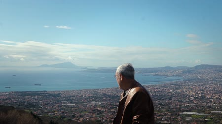 Happy handsome senior Caucasian local man enjoying incredible scenic view panorama of Naples from Vesuvius slow motion.