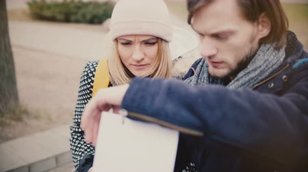 Happy young tourist Caucasian man and woman in warm winter clothes lost, looking at a city map travel guide together.